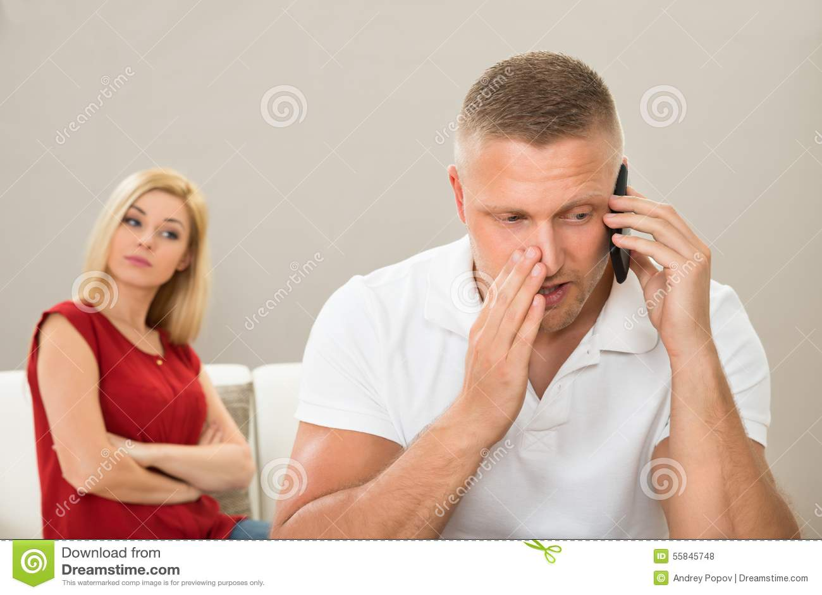 Esposa que olha o marido que fala no telefone celular