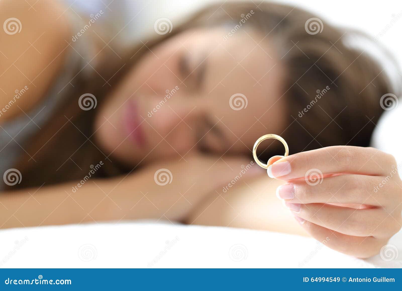 Esposa triste después del divorcio que lleva a cabo un anillo de bodas