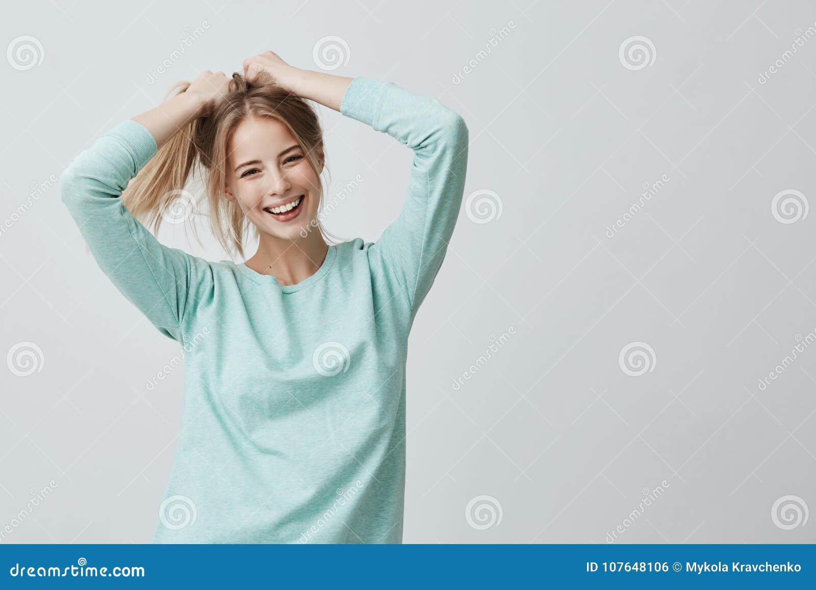 Espressioni ed emozioni del viso umano La giovane bella femmina positiva  con capelli diritti biondi tinti in coda di cavallo si è vestita in  abbigliamento ... e04cd35f6c94