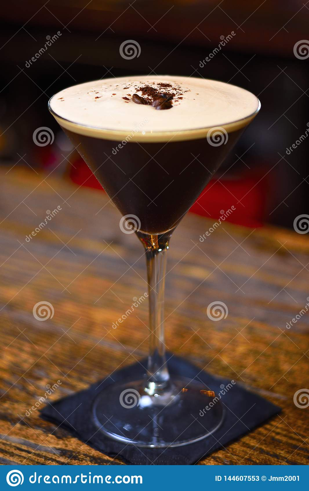 Espresso martini cocktail with coffee grains on bar