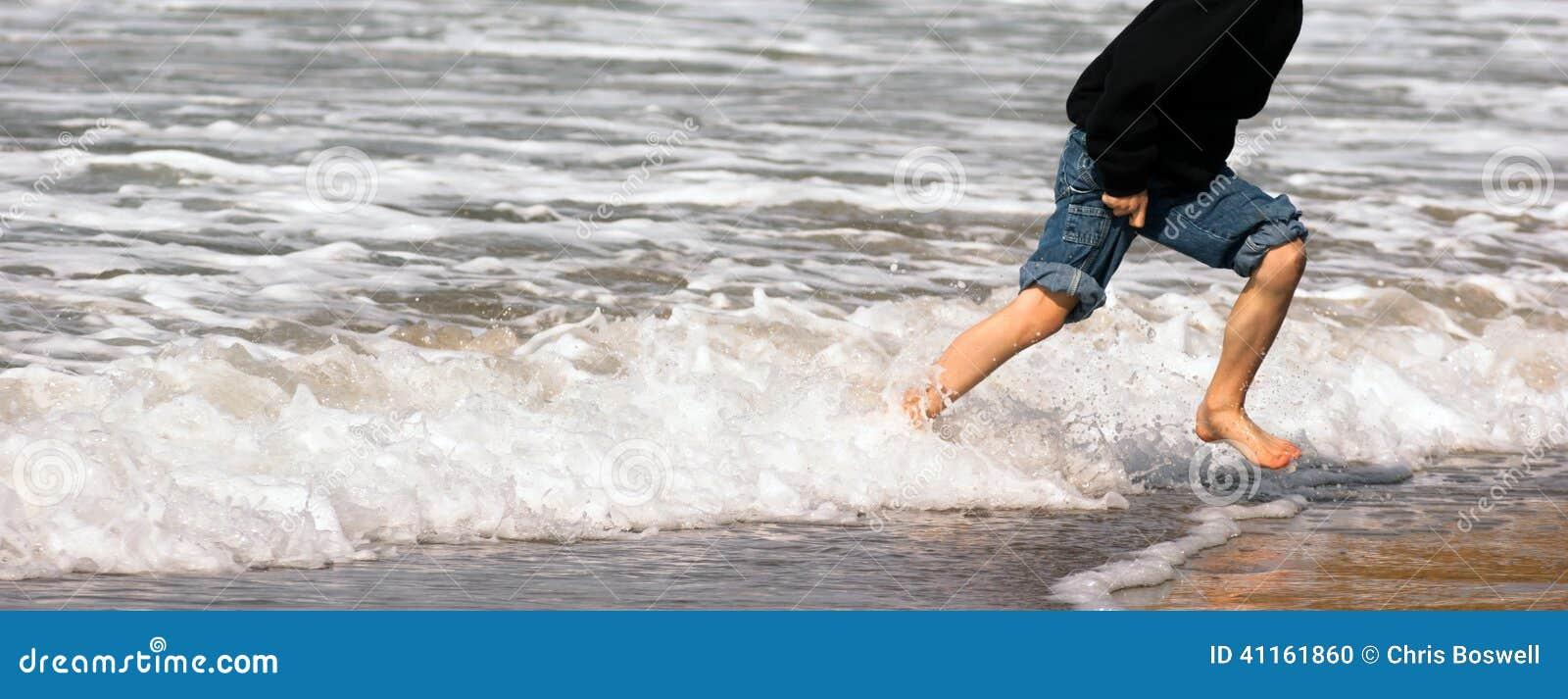 Espuma deixando de funcionar do mar da ressaca nova da praia do oceano dos pés running do menino