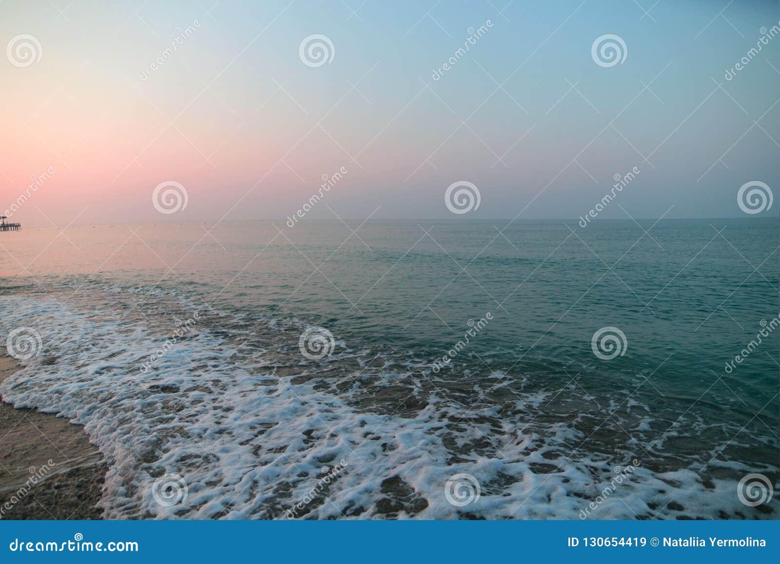 Espuma del mar en la playa Salida del sol en la playa