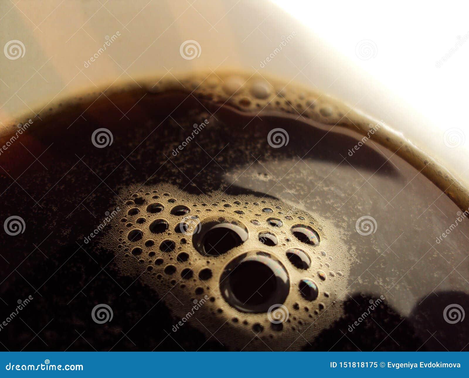 Espuma do café em um close up de vidro branco