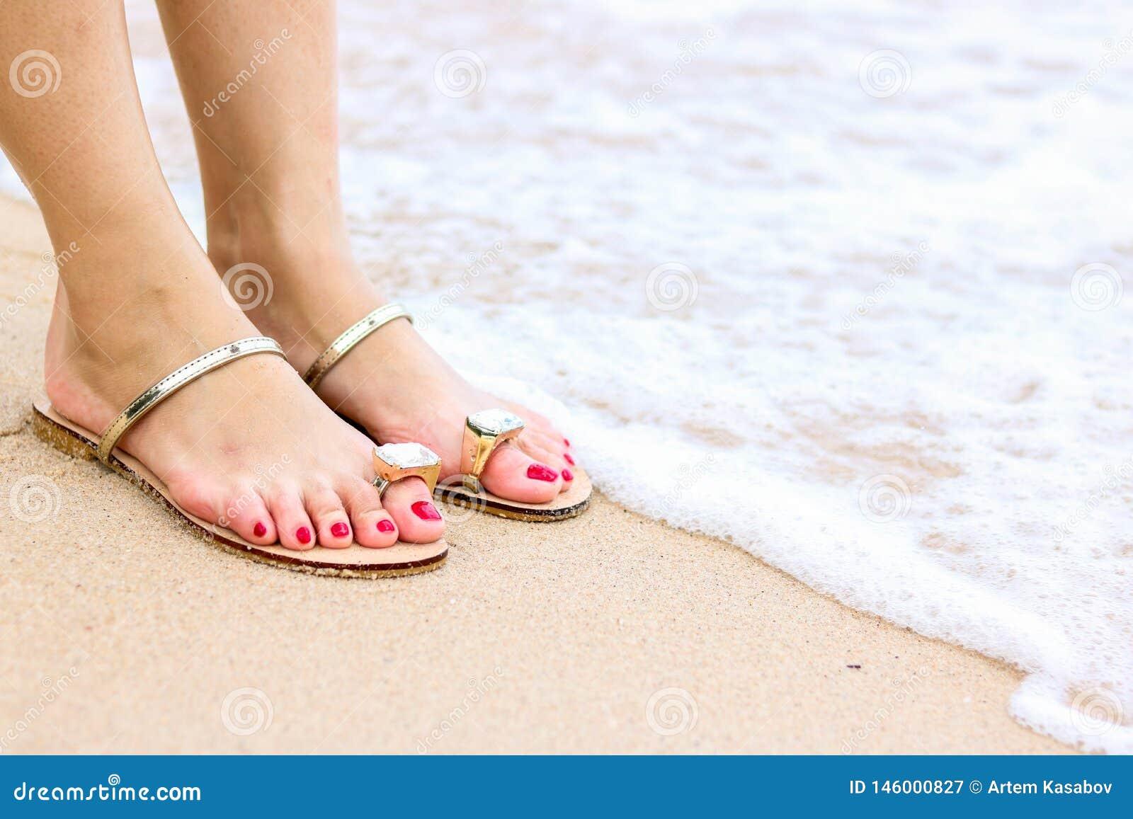 A espuma do mar, as ondas e os p?s despidos em uma areia encalham Os feriados, relaxam