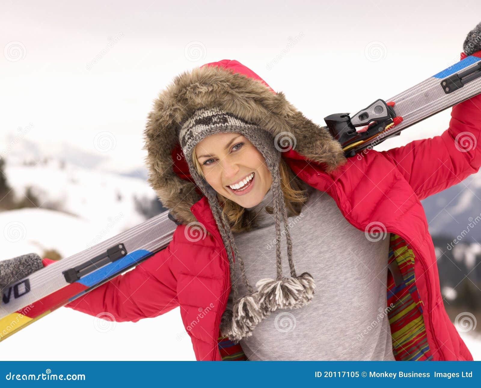 Esquís de la explotación agrícola de la mujer joven en paisaje alpestre