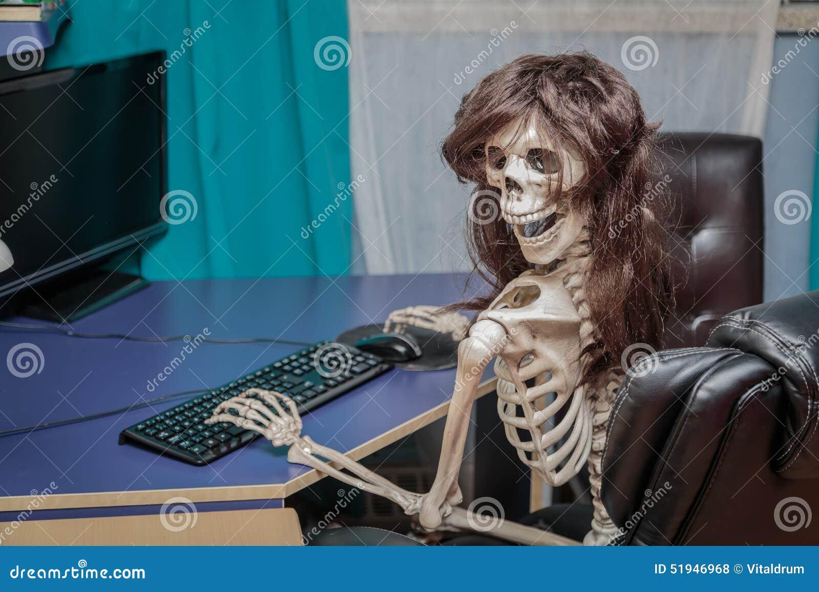 Esqueleto sonriente alegre en una peluca que se sienta en silla detrás del equipo de escritorio