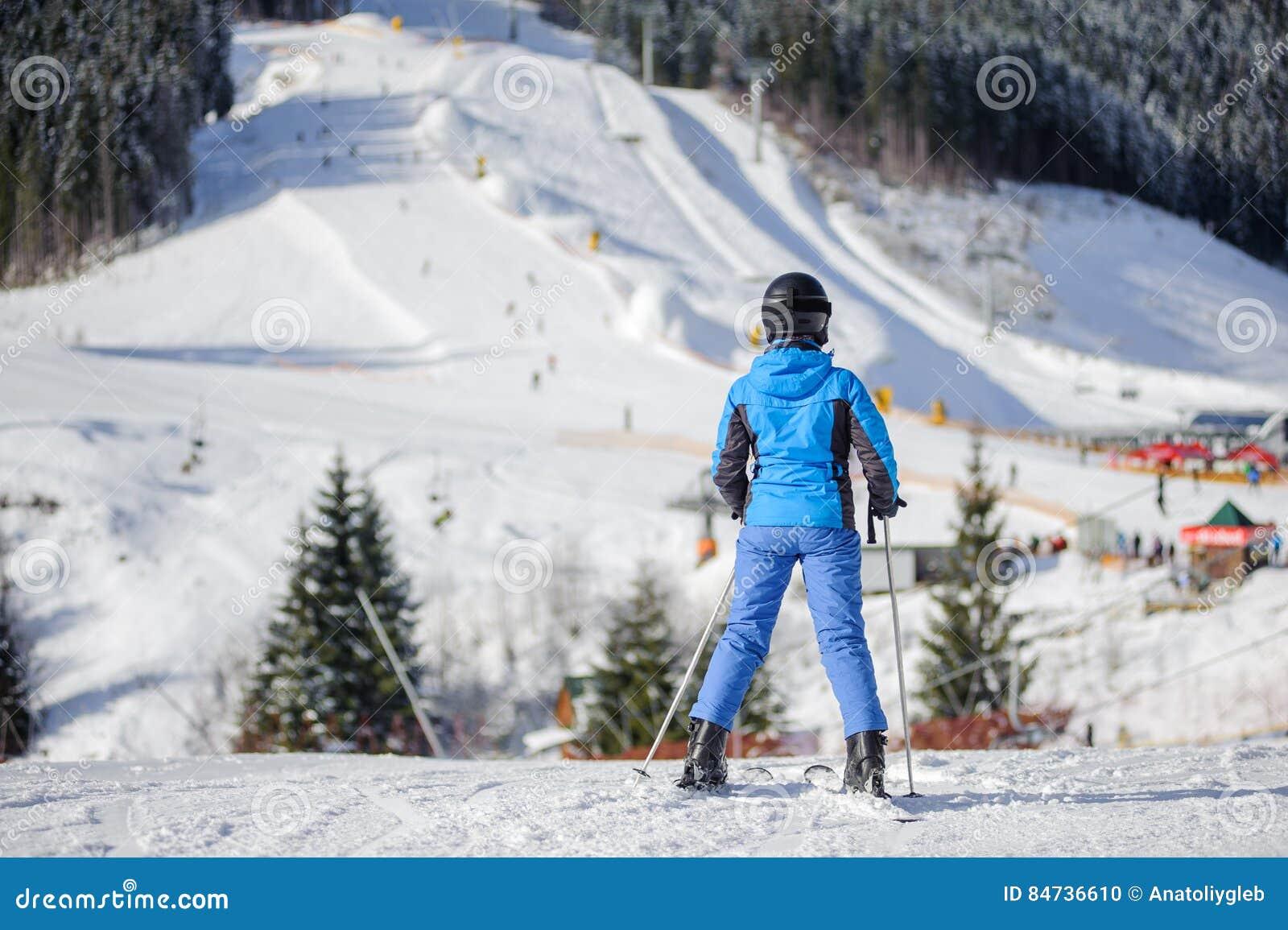 Esquiador de sexo femenino en una cuesta del esquí en un día soleado