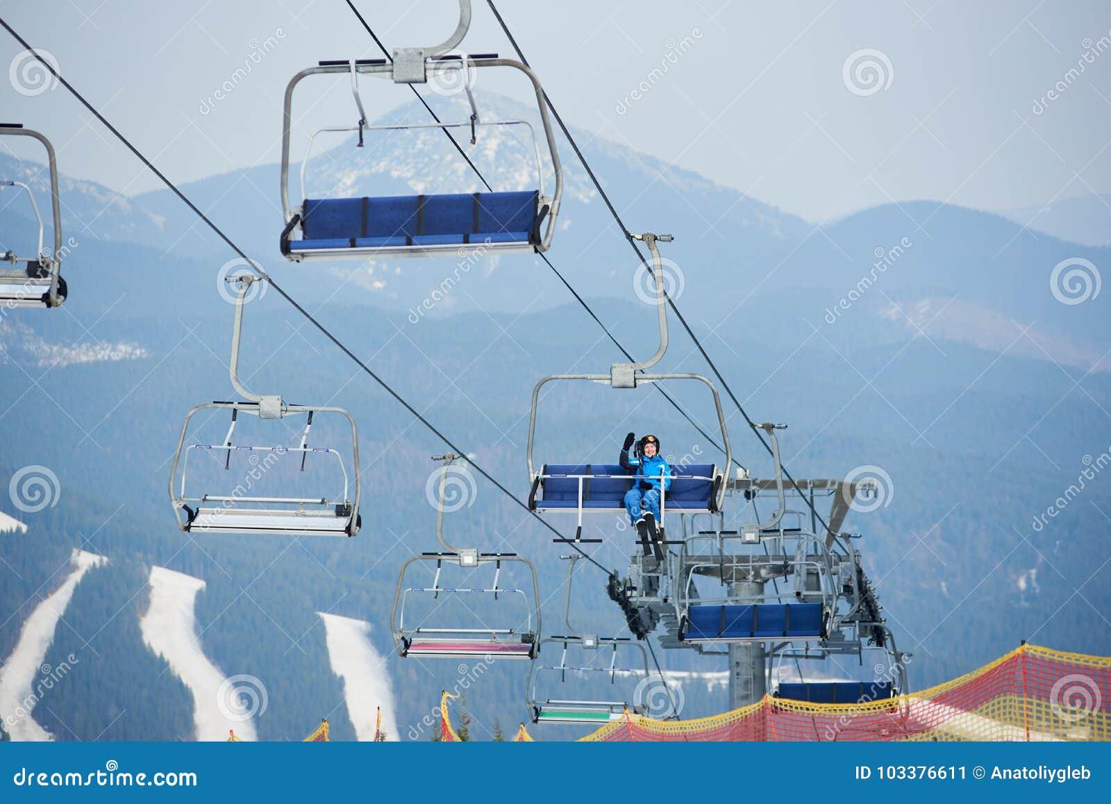 Esquiador de sexo femenino feliz en el traje de esquí azul que se sienta en un remonte del cable con los cielos en la estación de