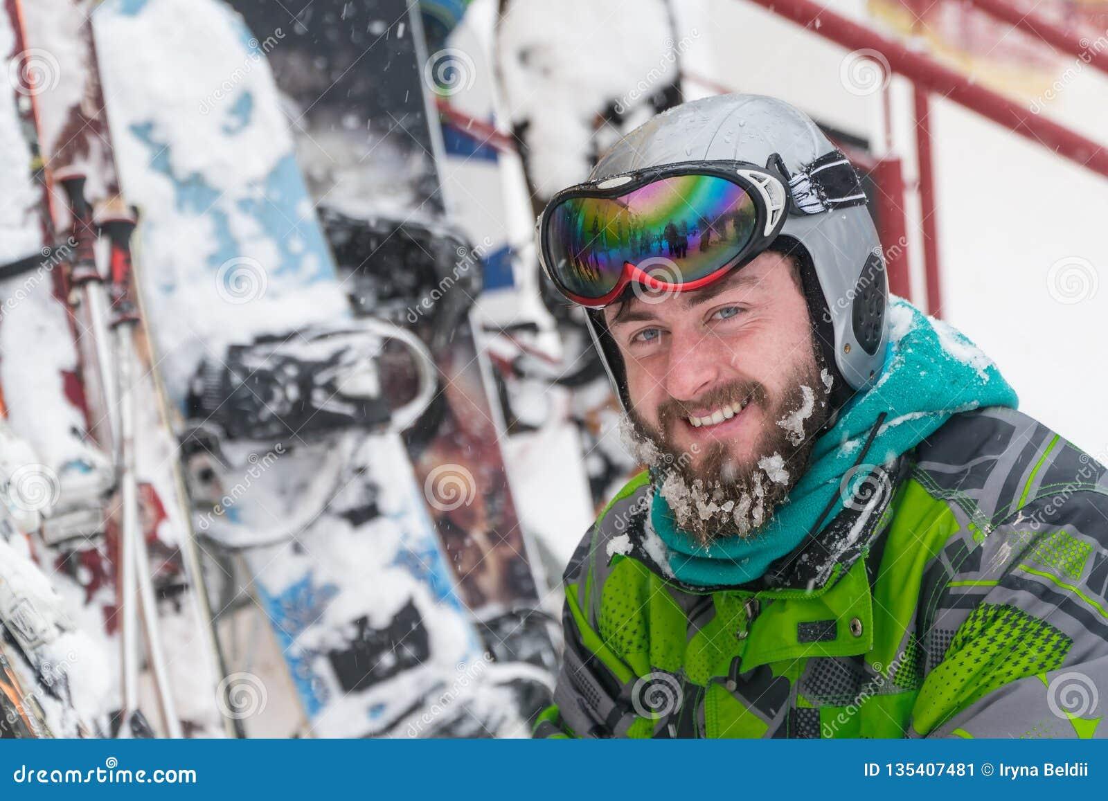 Esquiador en la máscara en la cara de un hombre de la nieve y de los esquís de la nieve
