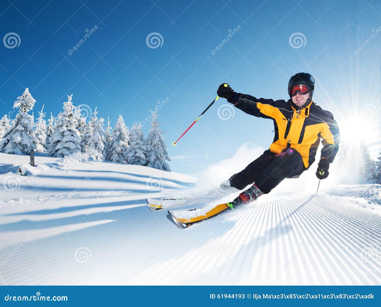 Esquiador en montañas, piste preparado y día asoleado