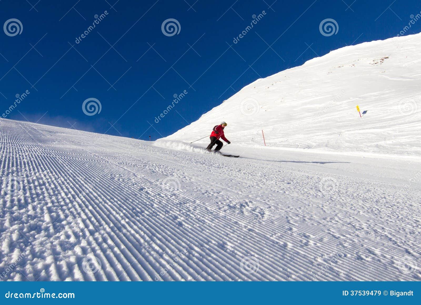 Esquiador na inclinação preparada do esqui