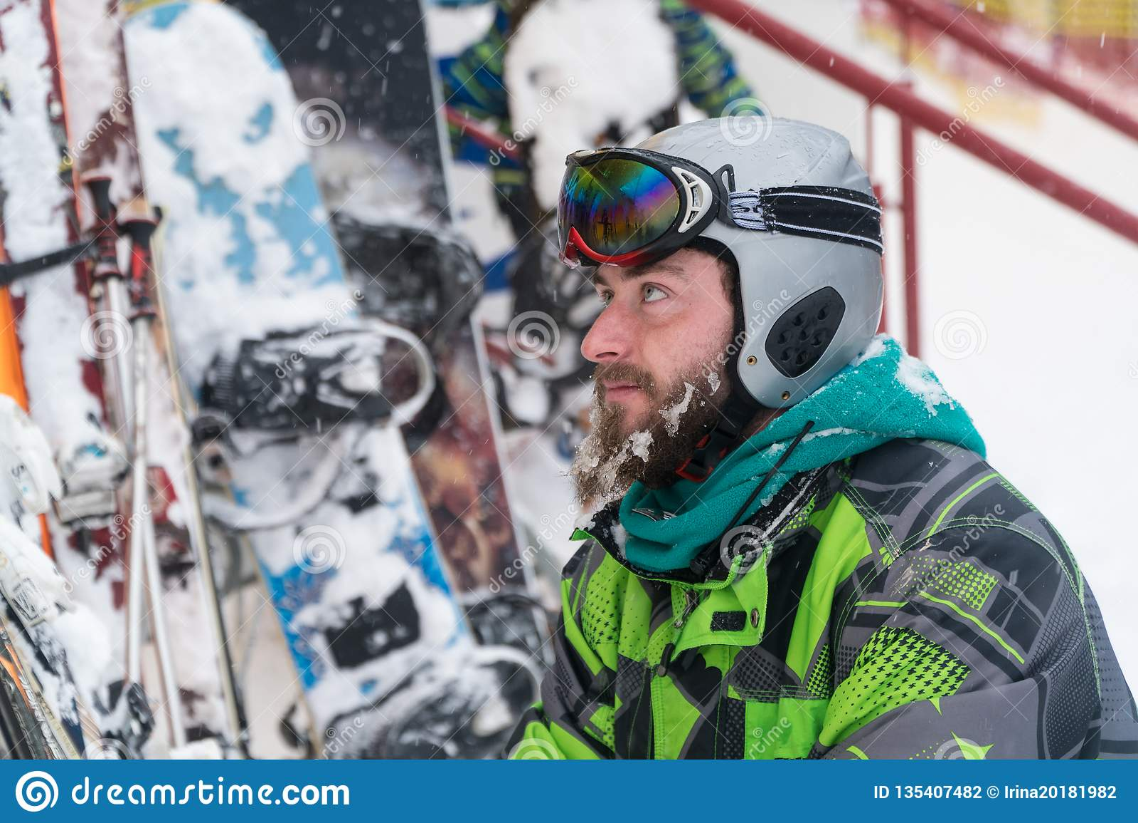 Esquiador na máscara na cara de um homem da neve e de esquis da neve