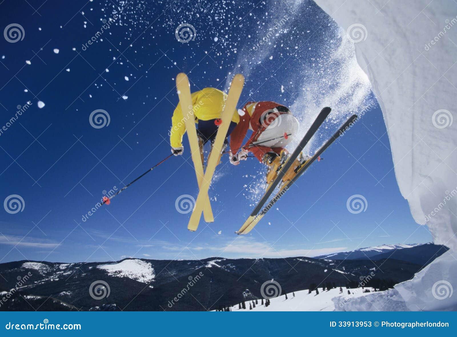 Esquiadores que lanzan del banco de la nieve que golpea las cuestas