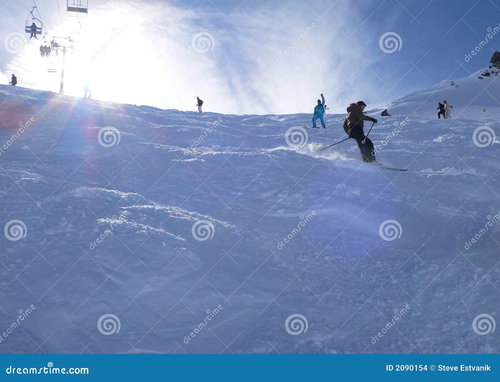 Esquiadores retroiluminados na neve do pó