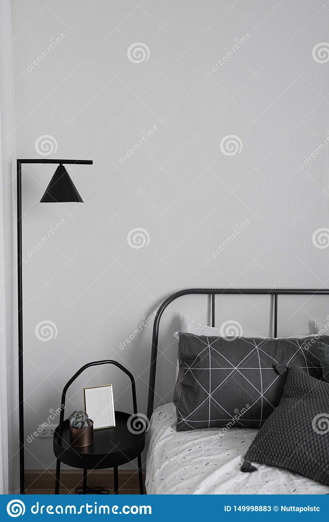 Esquina acogedora del dormitorio en estilo escandinavo con la decoración de la lámpara de pie mínima del metal negro/del diseño i