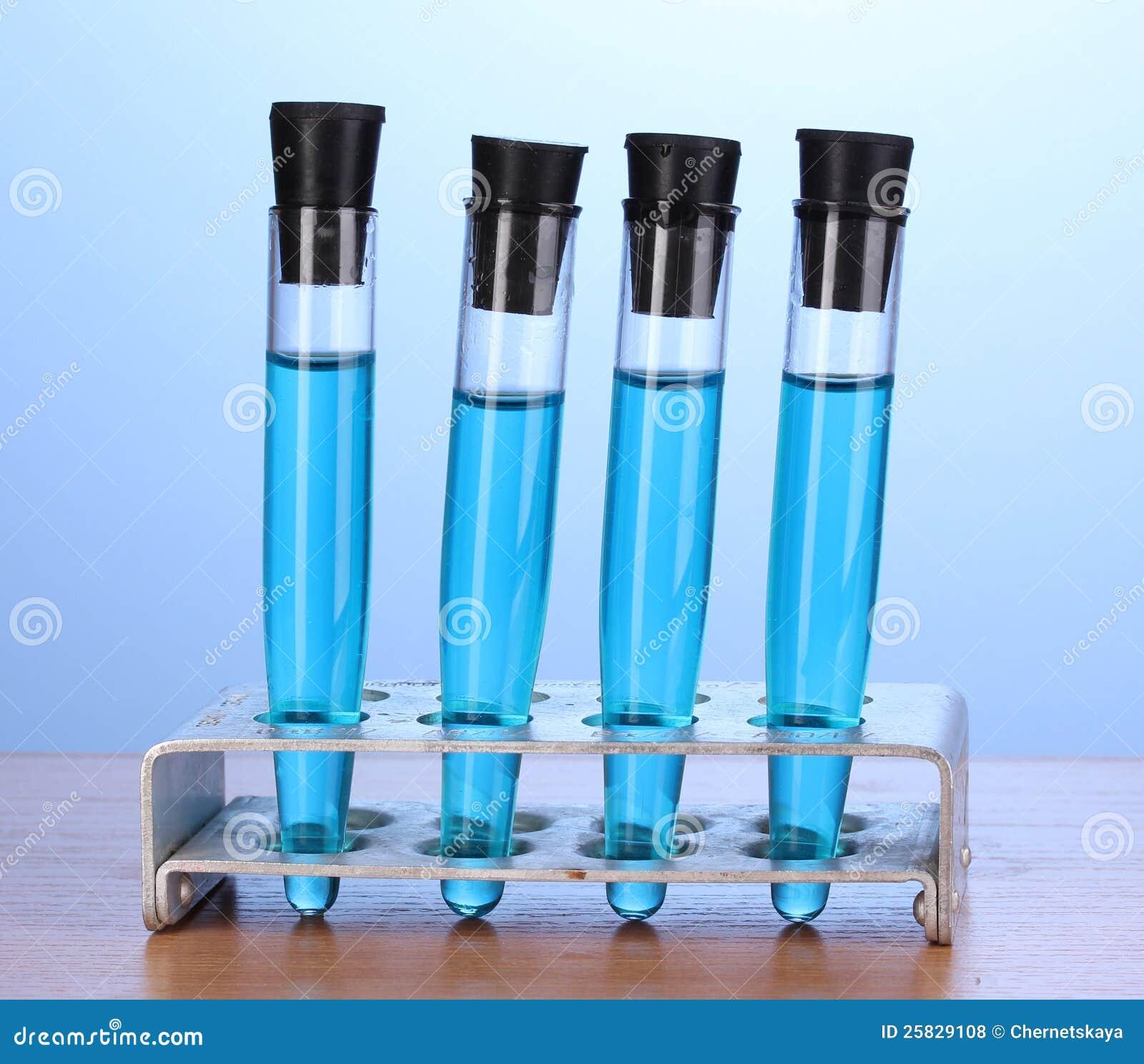 Essai-tubes avec le liquide bleu sur la table en bois sur le fond bleu