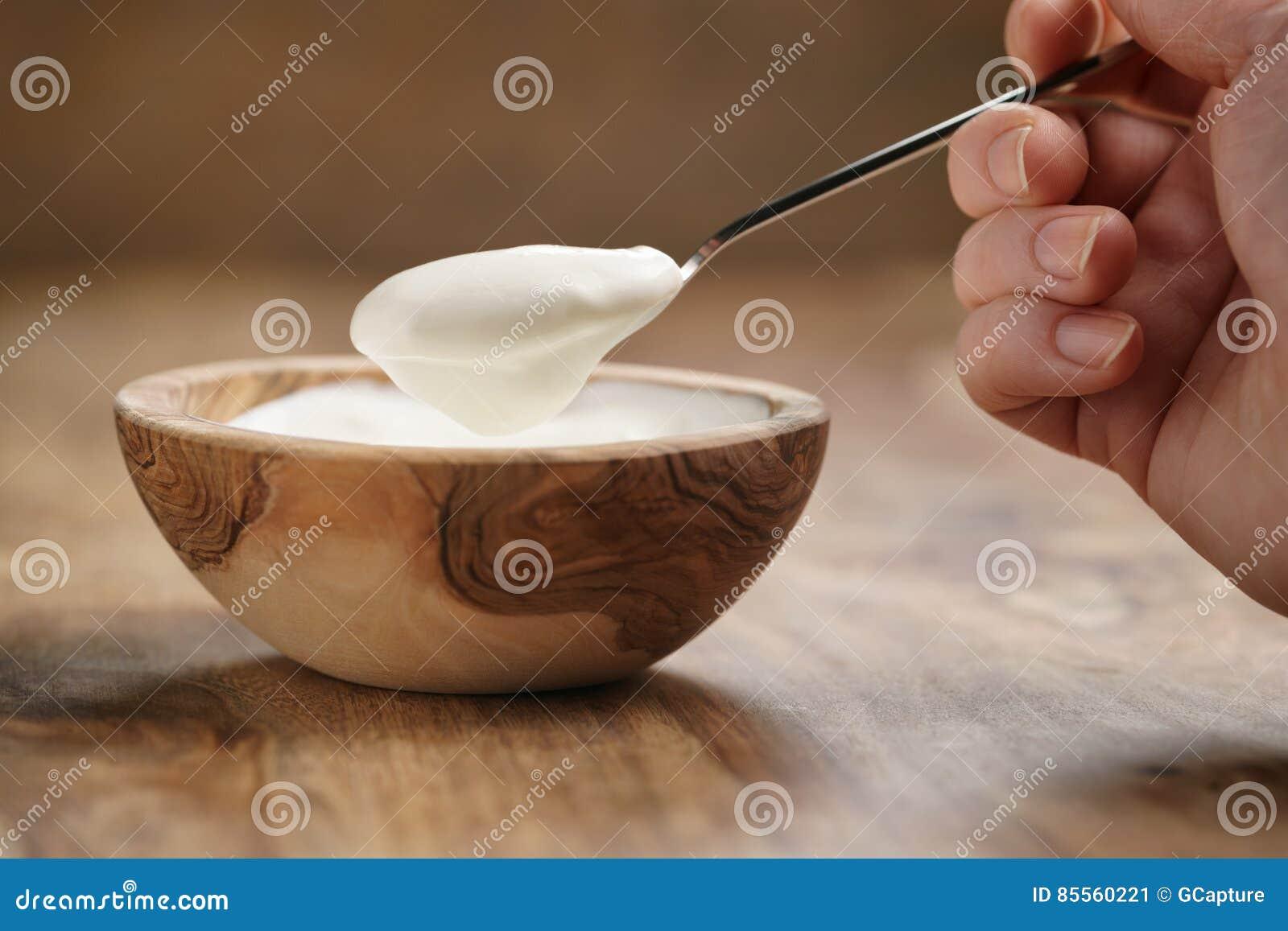 Essen des organischen Joghurts mit Löffel von der hölzernen Schüssel