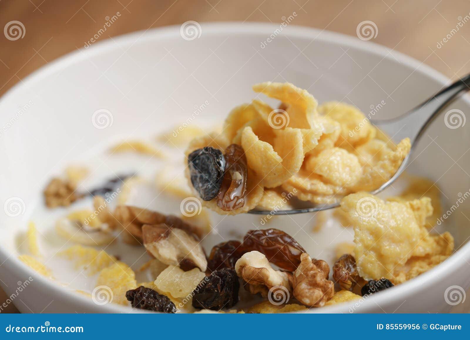 Essen von Corn Flakes mit Früchten und Nüssen in der weißen Schüssel