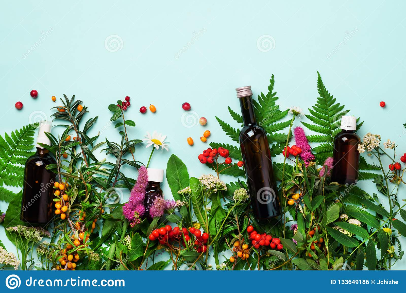 Essential oils in dark glass bottles and healing flowers, herbs on blue background. Holistic medicine approach. Healthy food