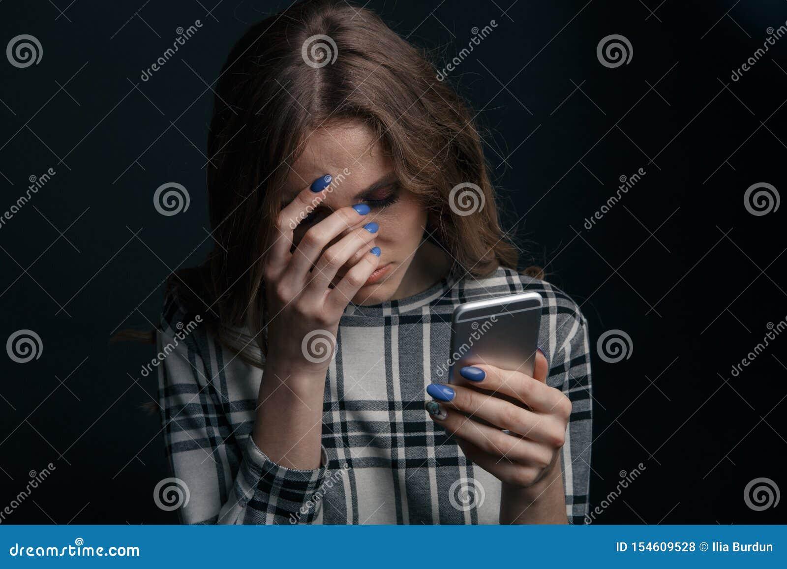 Essere teenager triste vittima del cyberbullismo online che si siede su uno strato nel salone a