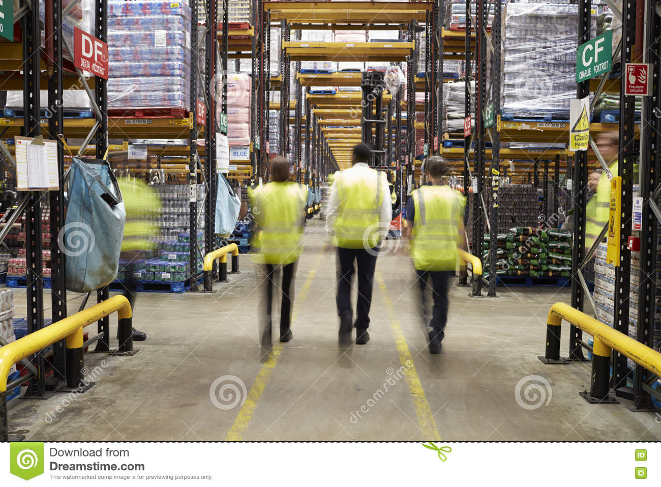 ESSEX, ENGLAND- MAR 13 2016: Staff in reflective vests walking away from camera in a supermarket distribution warehouse