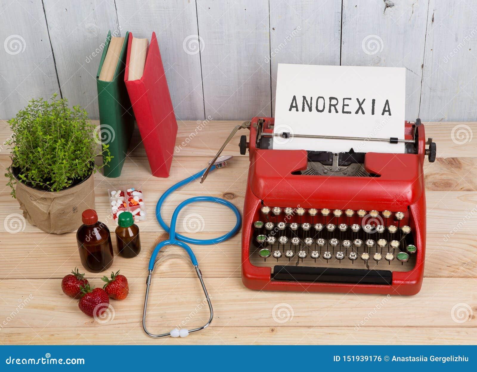 Essstörungskonzept - Schreibmaschine mit Text Magersucht, blaues Stethoskop, Pillen, rote Schreibmaschine, Erdbeeren