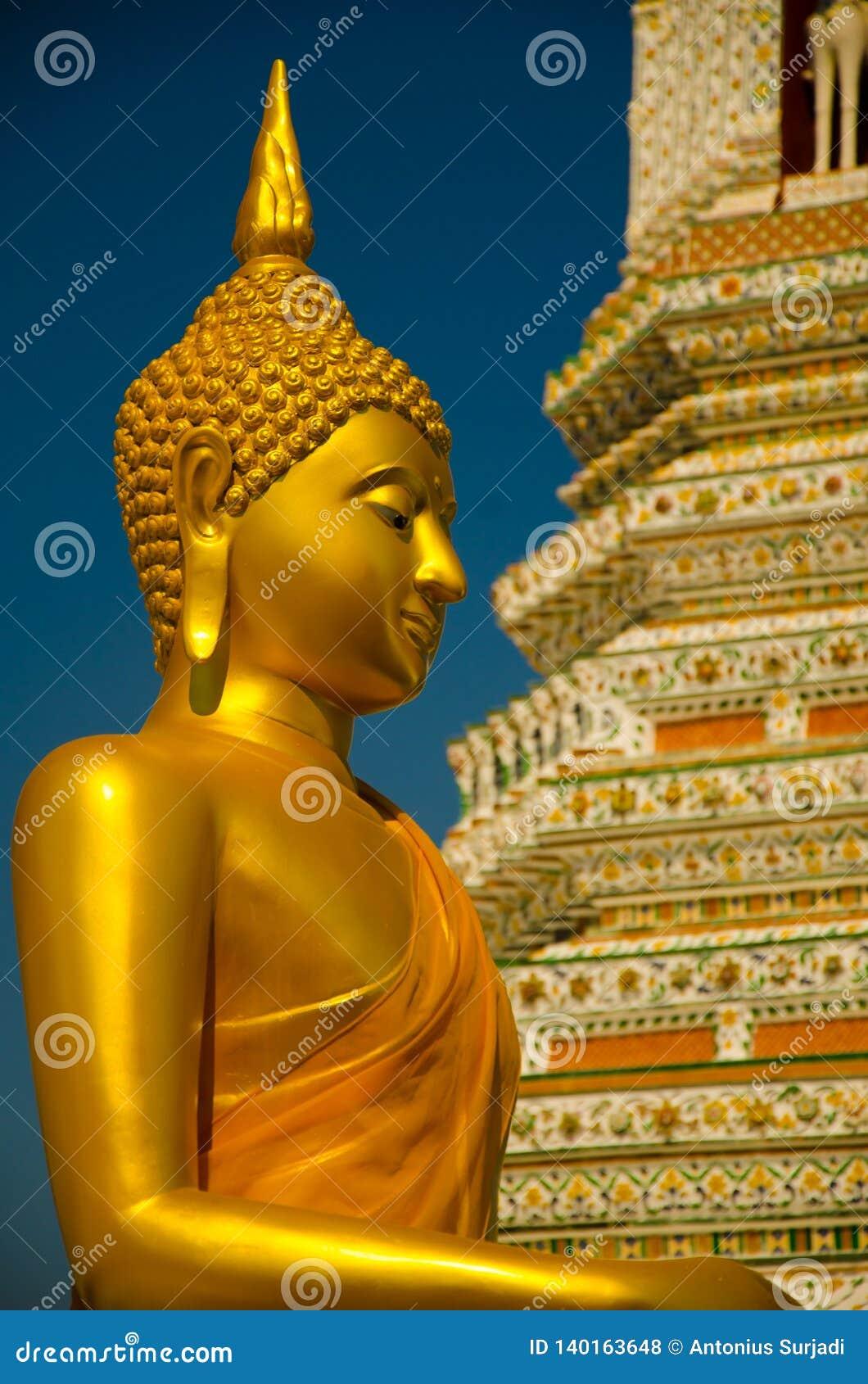 Estátua amarela dourada da Buda que senta-se que medita e que reza