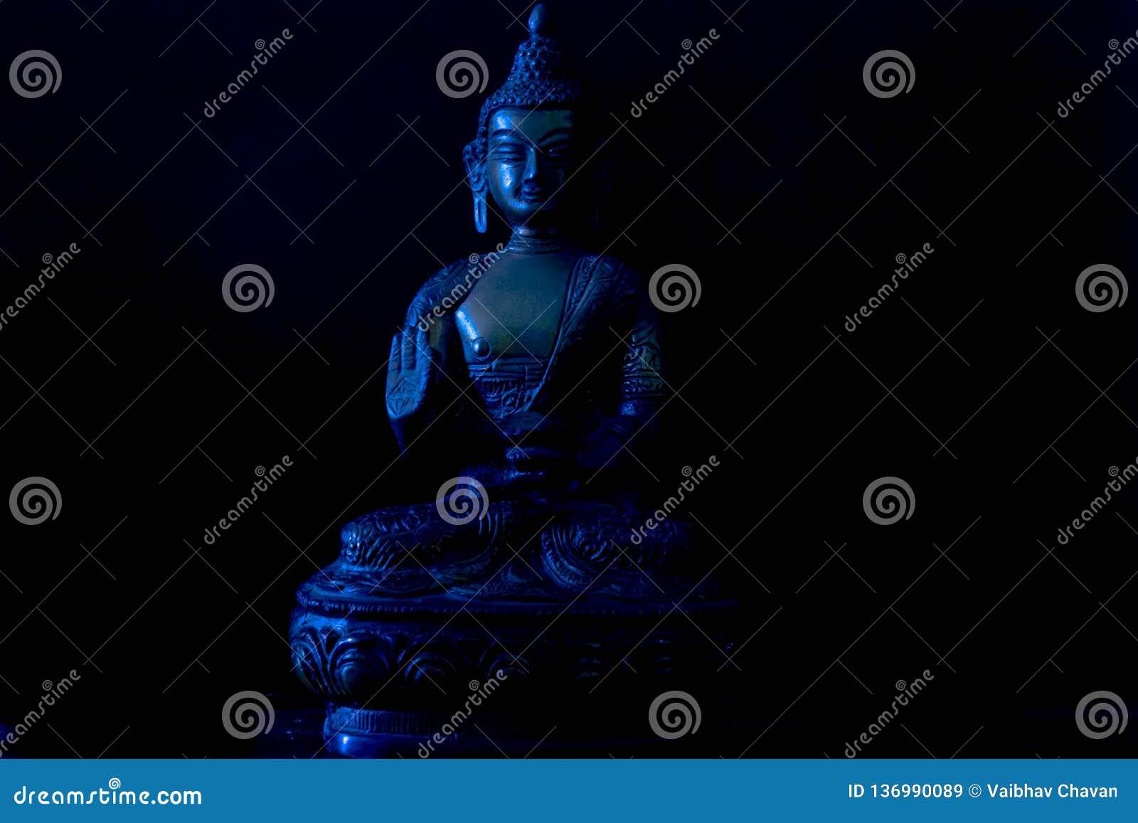 Estátua antiga do metal da Buda no fundo preto