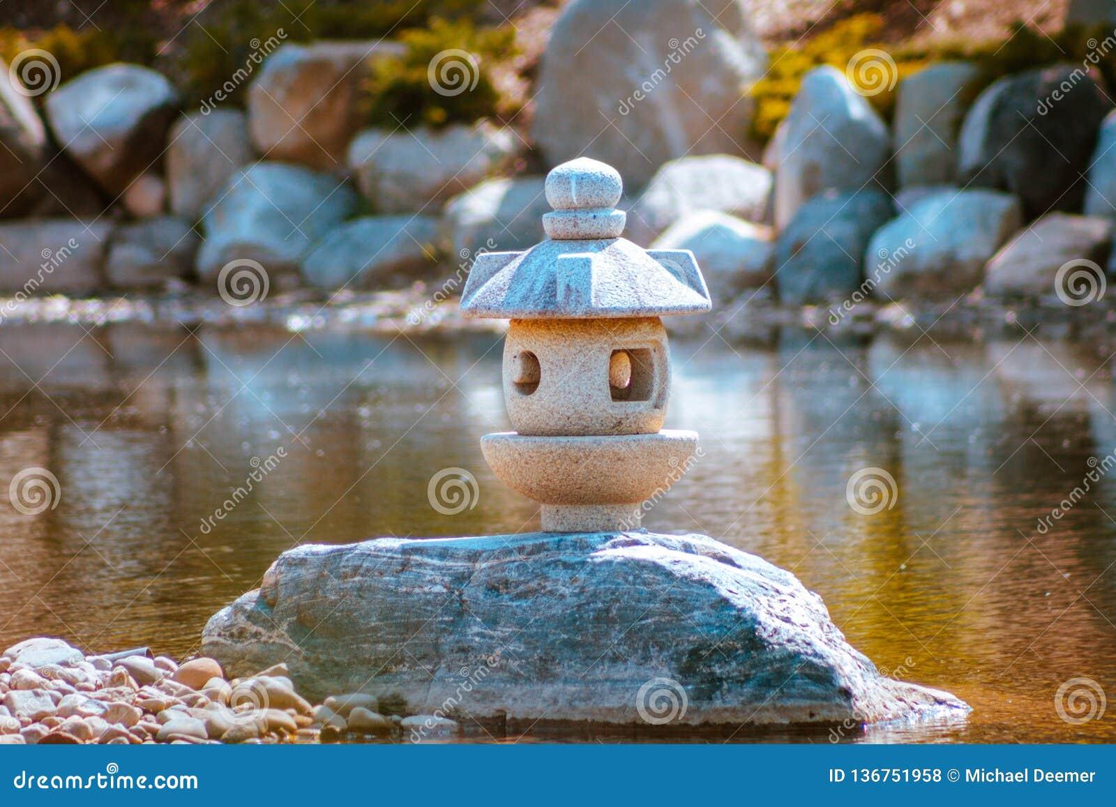 A estátua da lanterna japonesa está sozinha em uma península nos jardins japoneses