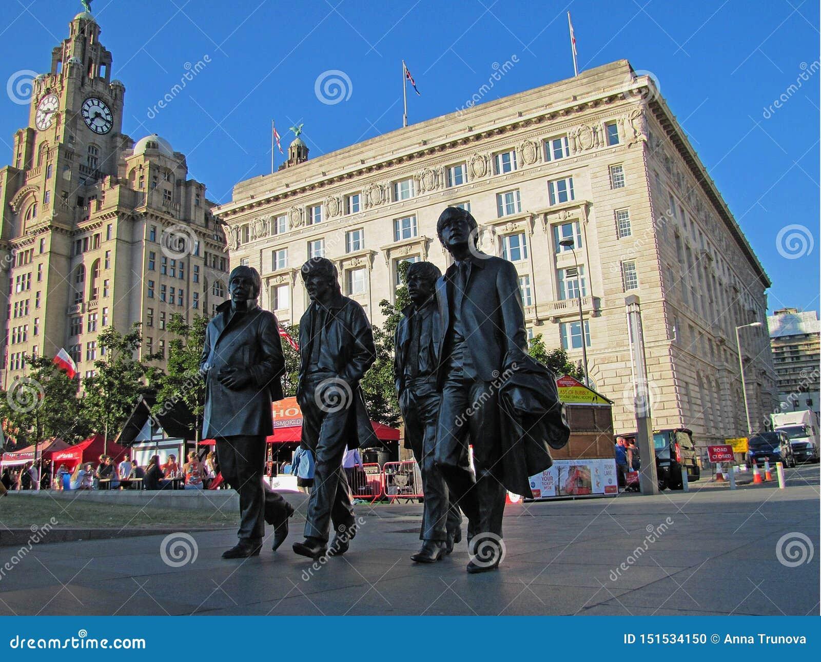 Estátua de bronze que representa o Beatles que anda ao longo da rua em Liverpool