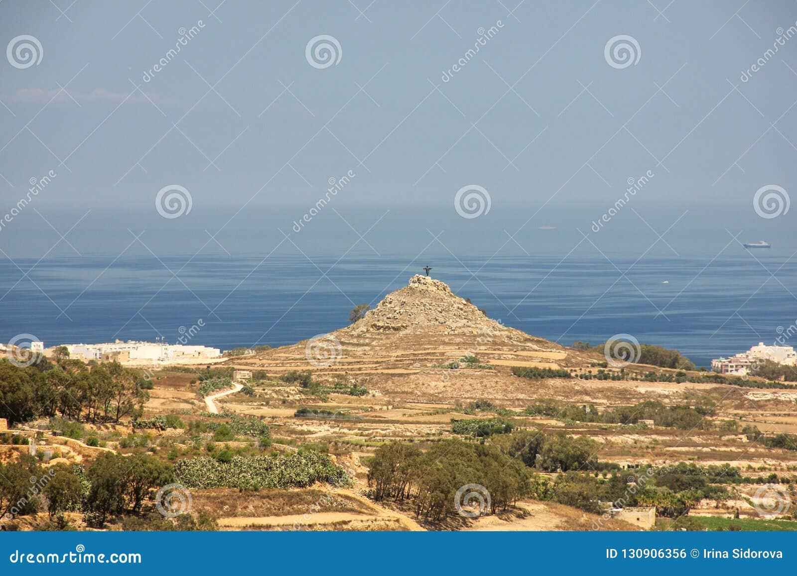 Estátua de Cristo o salvador na parte superior do monte no fundo do mar azul infinito