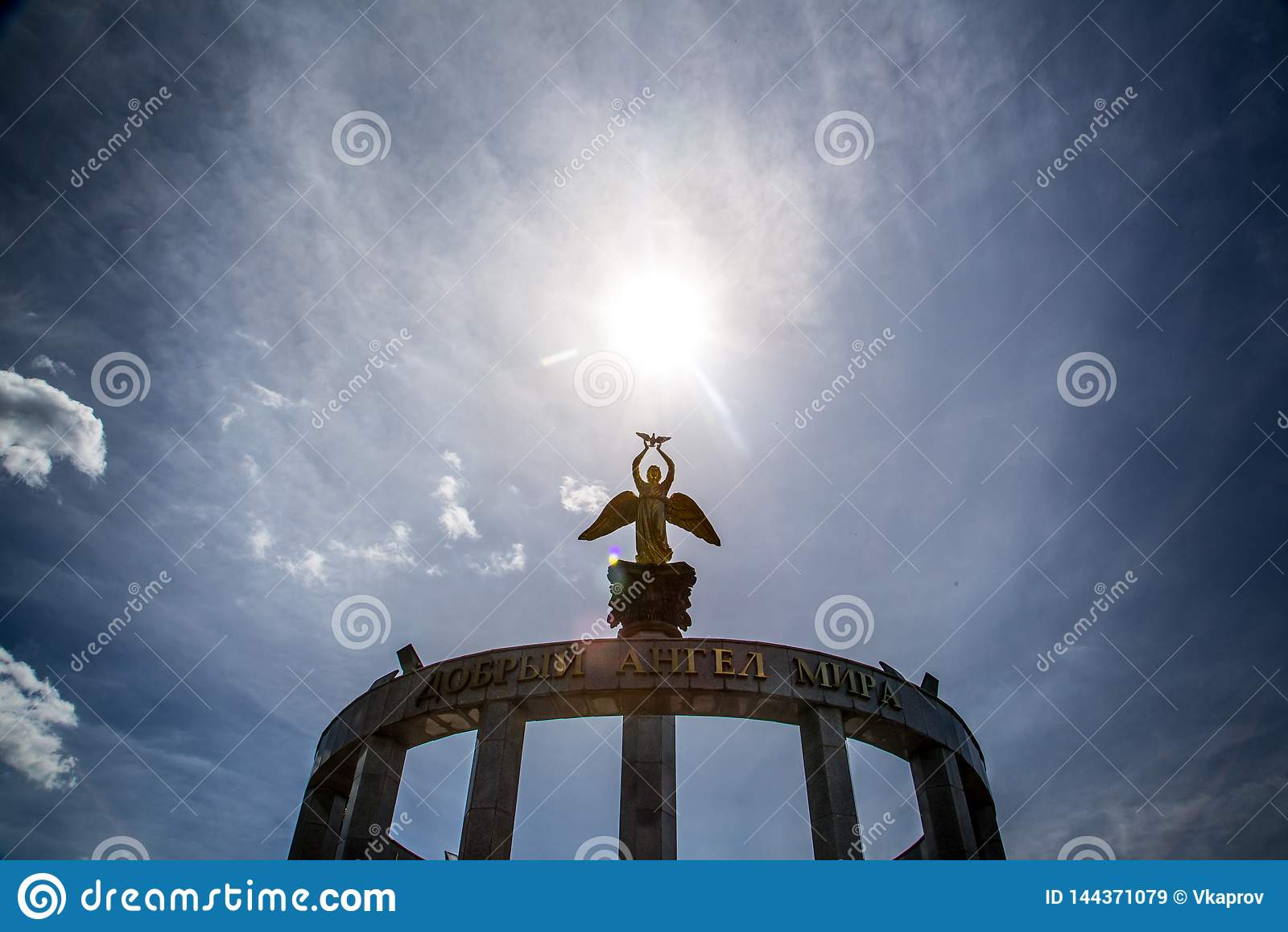 Estátua de um anjo e o sol acima dele