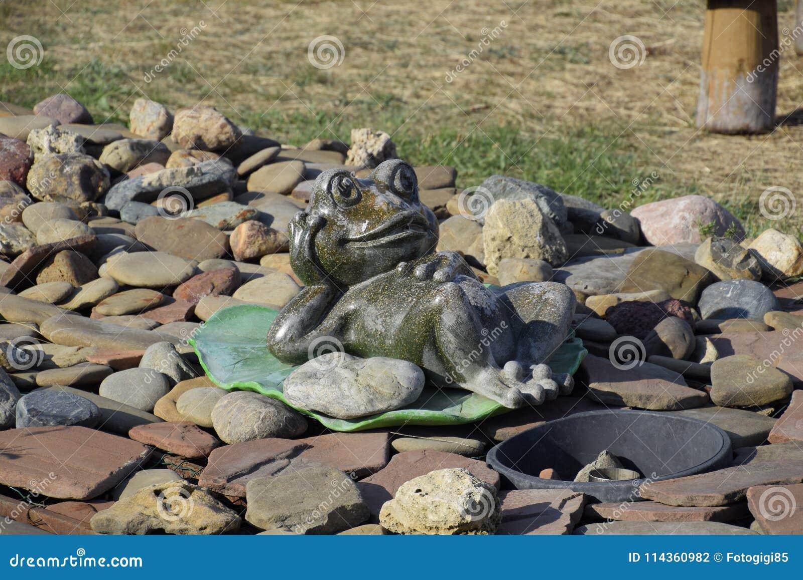 Estátua de uma rã em um lírio de água Uma estátua em seixos