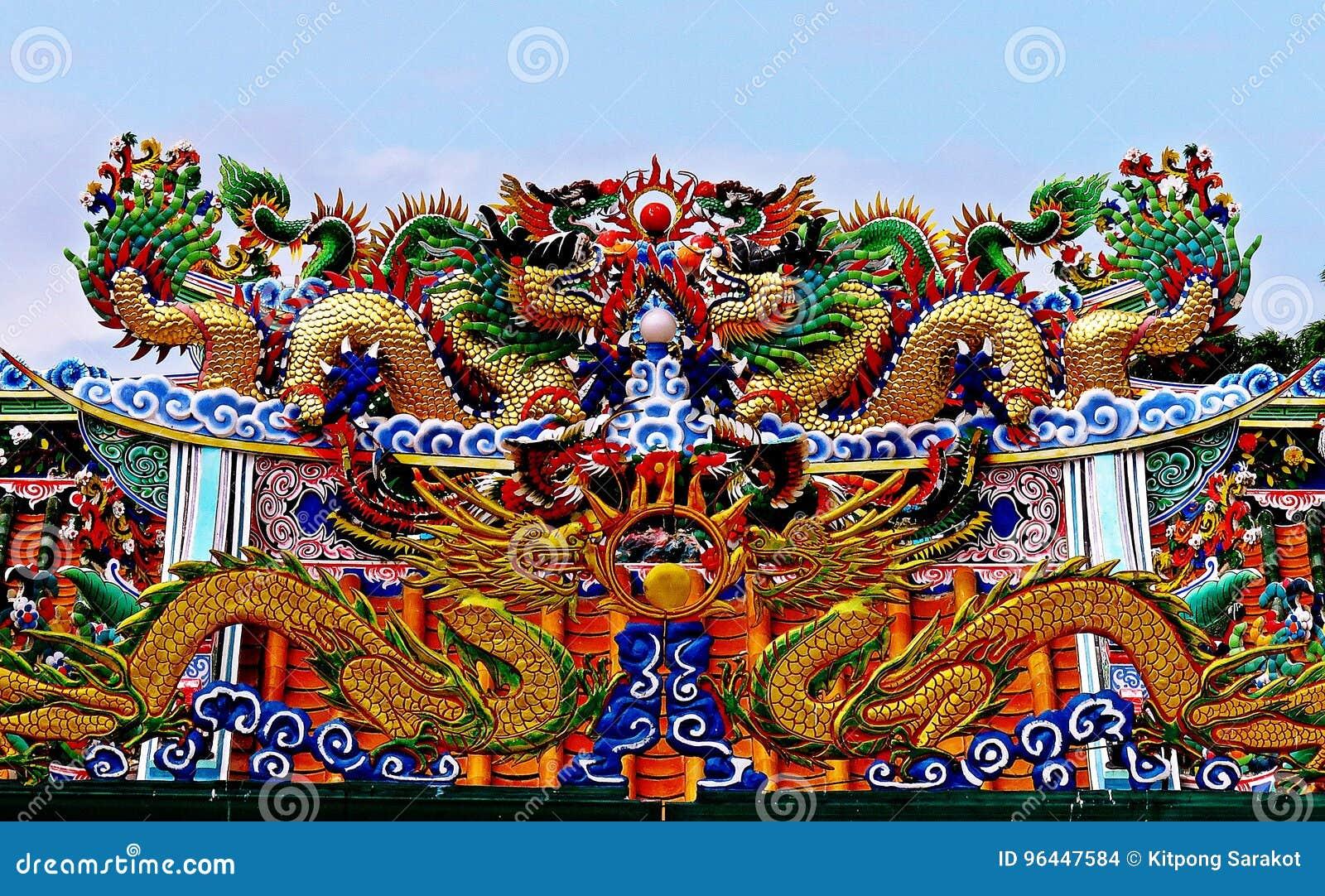 Estátua do dragão que voa o telhado chinês do templo em Tailândia