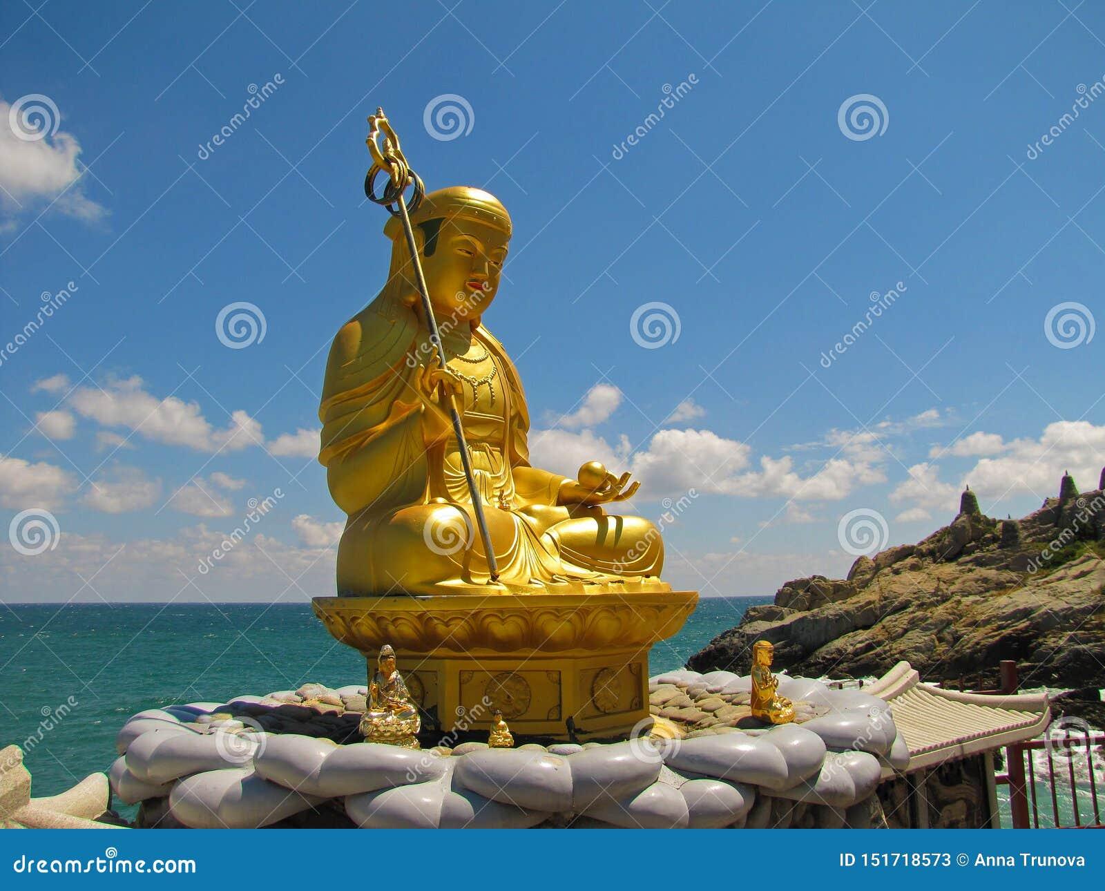 Estátua dourada de um deus que senta-se pelo oceano