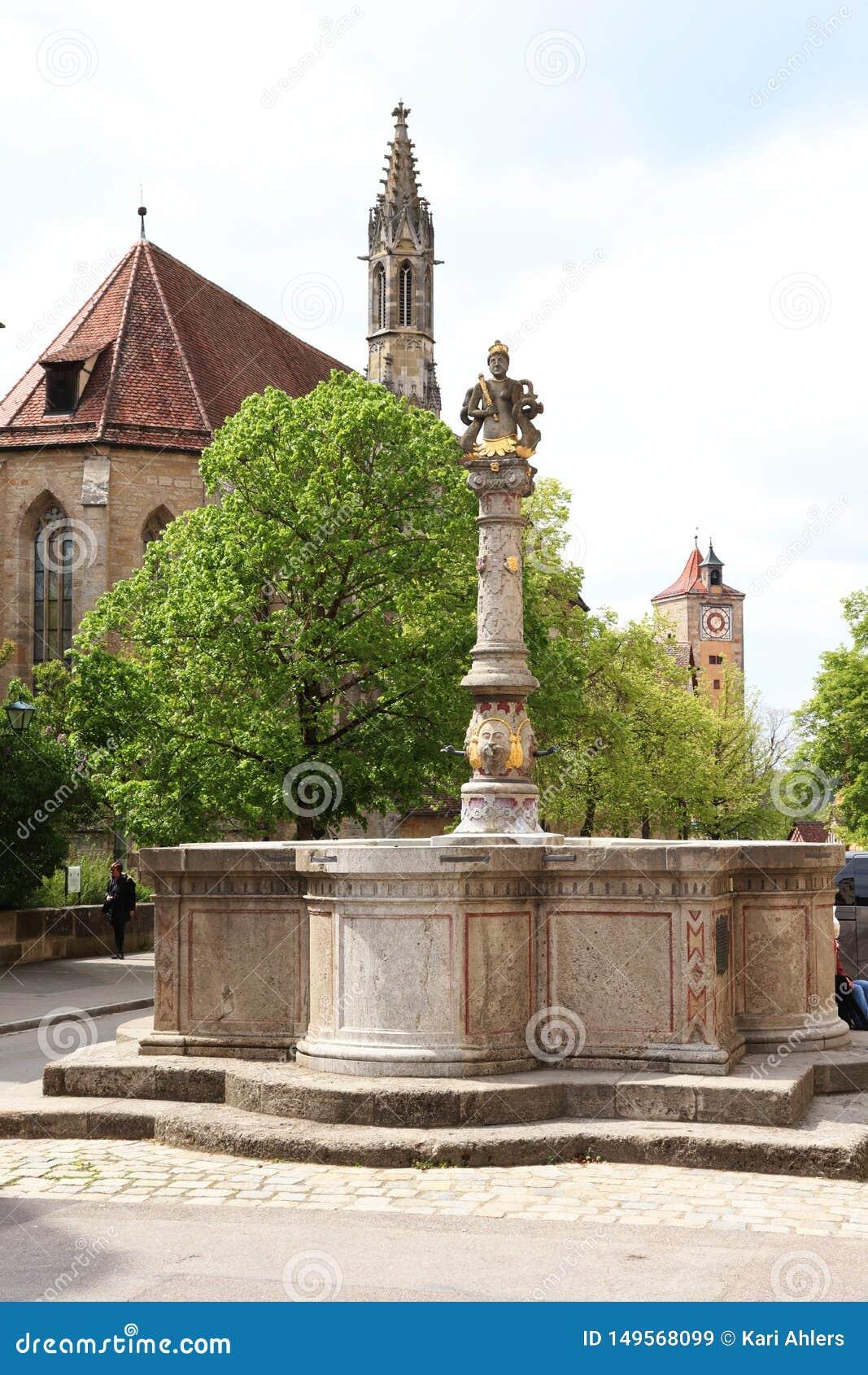 Est?tua, igreja e torre no der Tauber do ob de Rothenburg, Alemanha