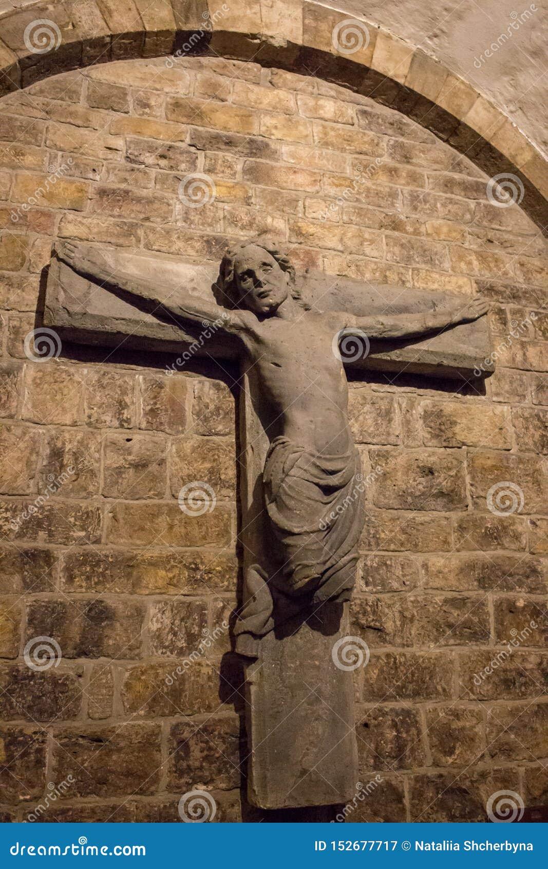 Estátua quebrada antiga de Jesus Christ na parede Cruz de pedra medieval na igreja medieval Decoração antiga da cripta