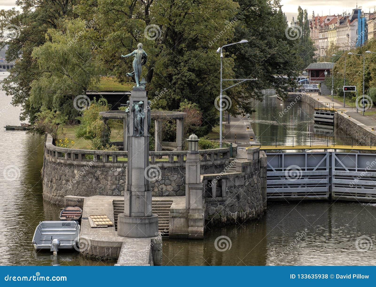 Estátuas de bronze de mulheres despidas em uma coluna de pedra, rio de Vlatava perto da ponte lateral da legião de Lesser Town, P