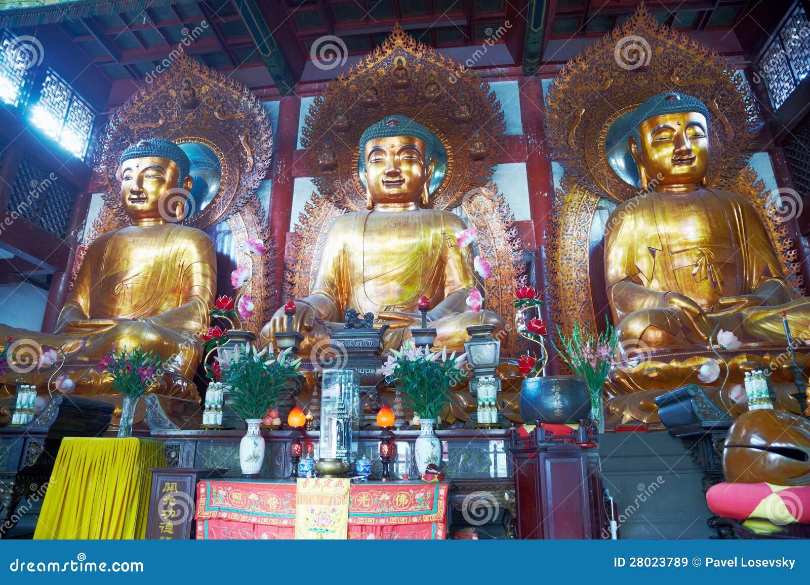 Estátuas de três Buddhas no templo