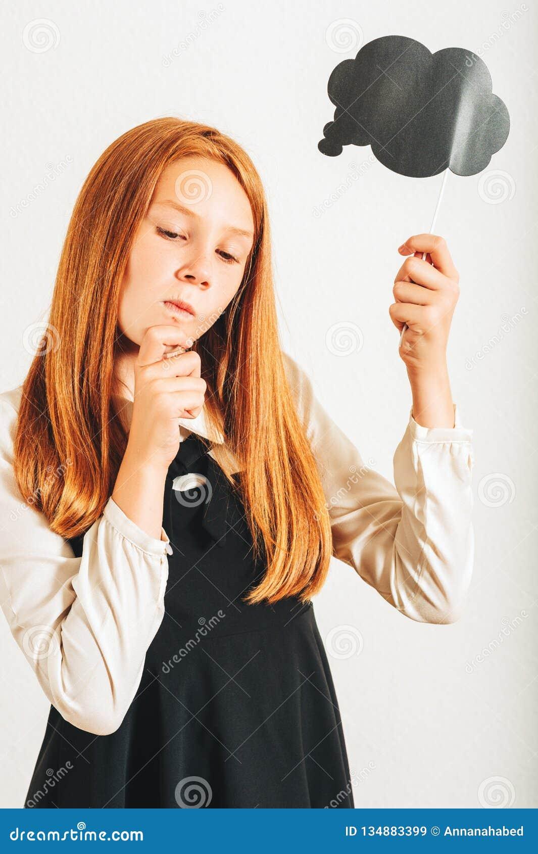 Estúdio disparado da menina ruivo nova da criança que guarda a bolha de pensamento do papel