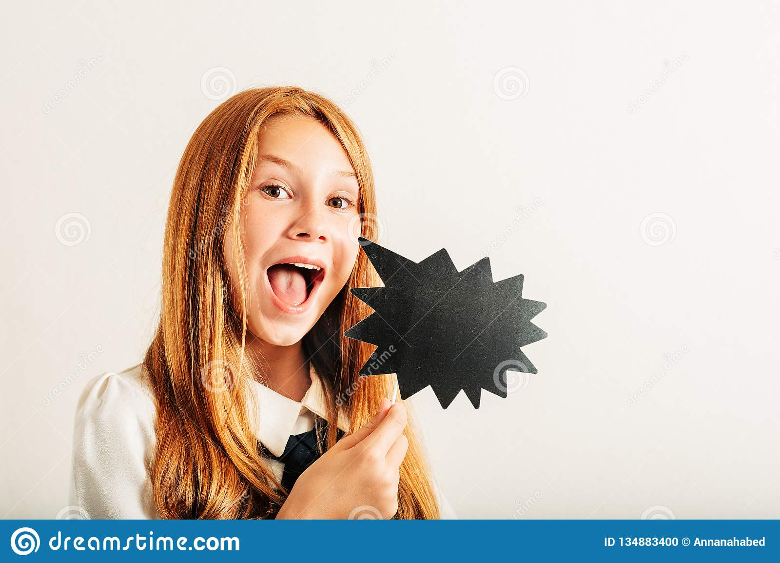 Estúdio disparado da menina ruivo nova da criança que guarda a bolha do discurso do papel