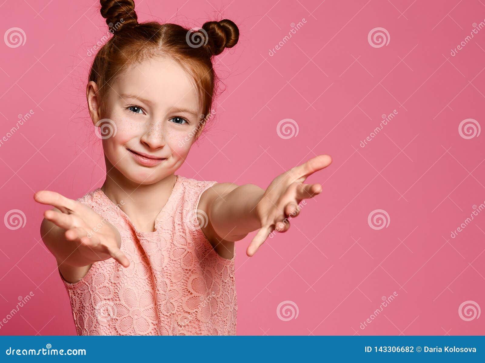 Estúdio disparado de uma menina bonito amigável do ruivo que puxa as mãos para