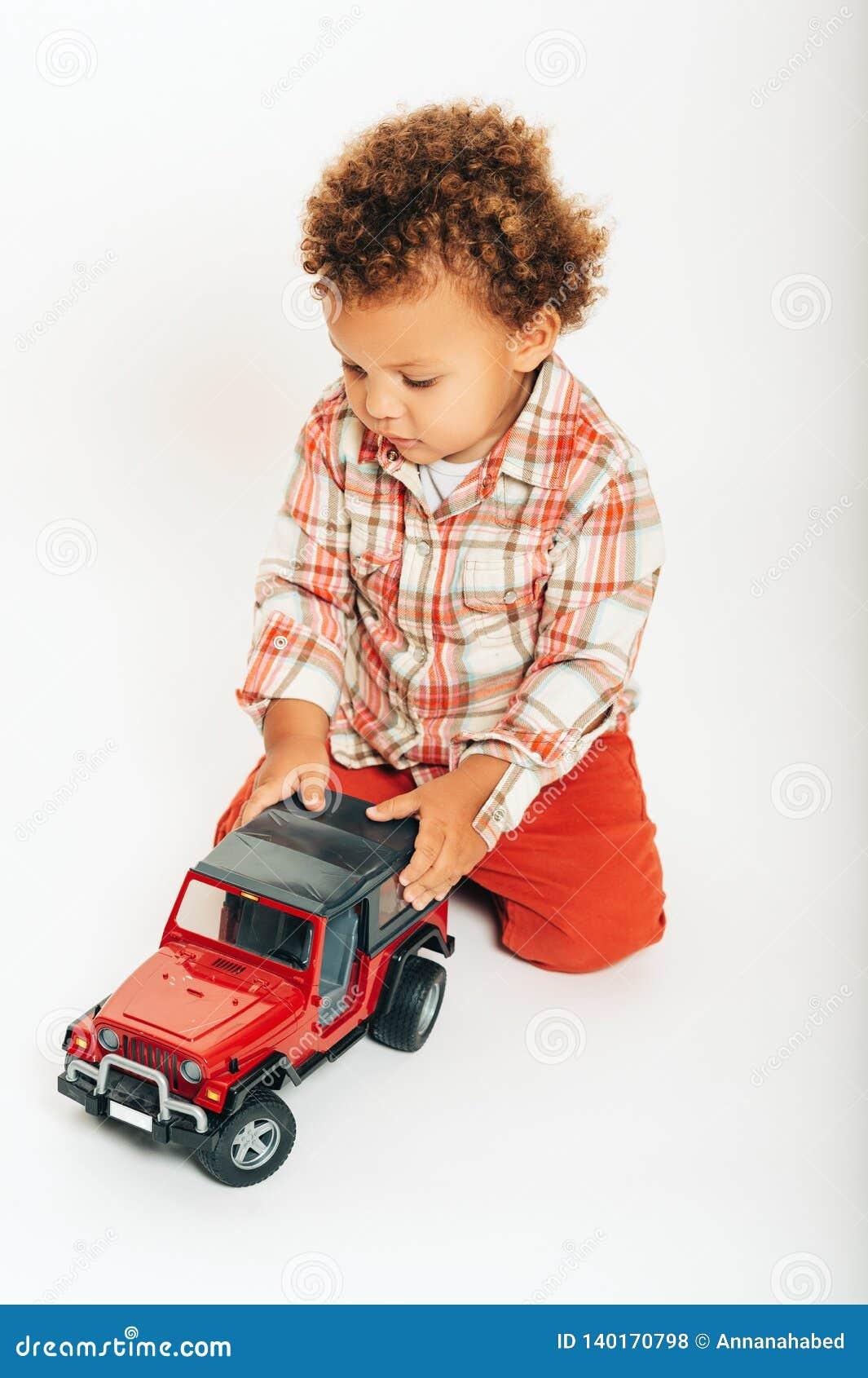 Estúdio disparado do bebê africano adorável do bebê de um ano que joga com carro