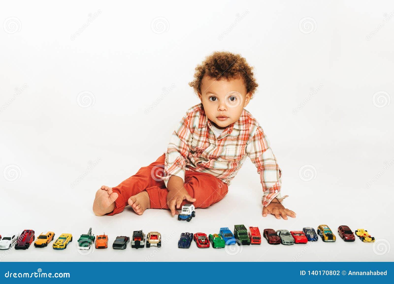 Estúdio disparado do bebê africano adorável do bebê de um ano que joga com carros coloridos