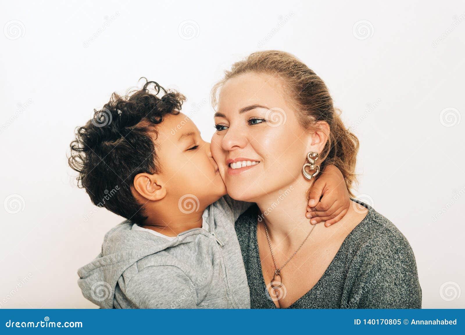 Estúdio disparado do menino adorável da criança que dá um beijo a sua mãe