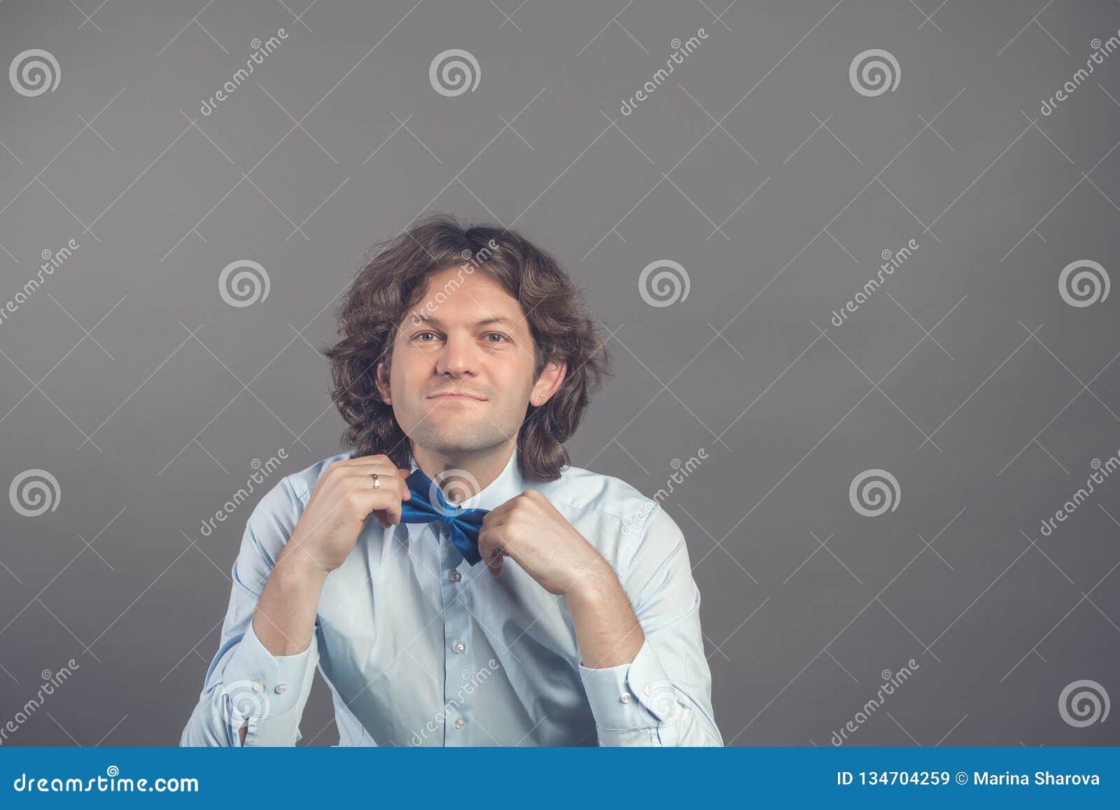 Estúdio disparado do moderno masculino novo que ajusta seu laço no espelho isolado no fundo cinzento Noivo escuro do cabelo encar