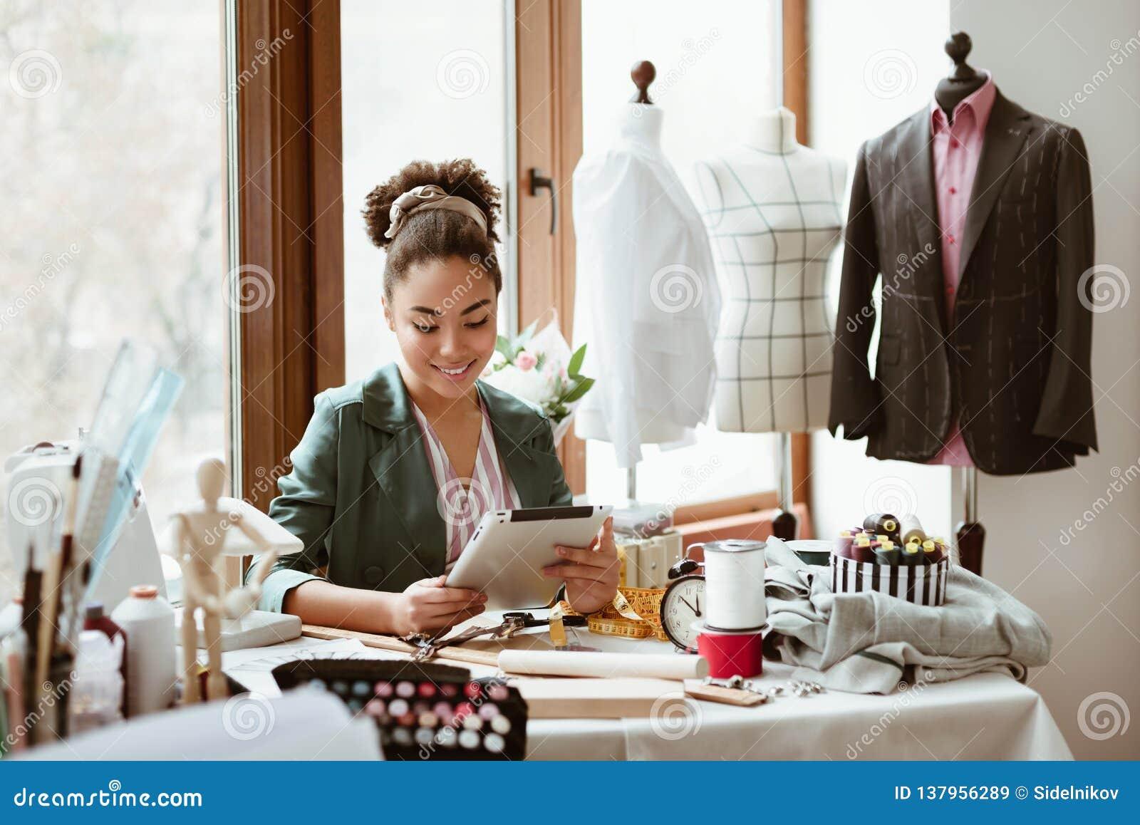 Estúdio do projeto O alfaiate da jovem mulher com tabuleta digital está modelando a roupa nova