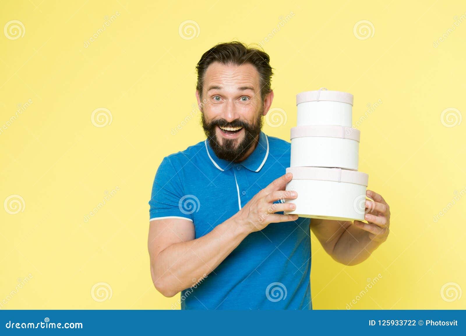 Est il tout pour moi Les présents rendent la vie plus intéressante Le visage gai barbu mûr d homme tient des boîtes de pile Homme