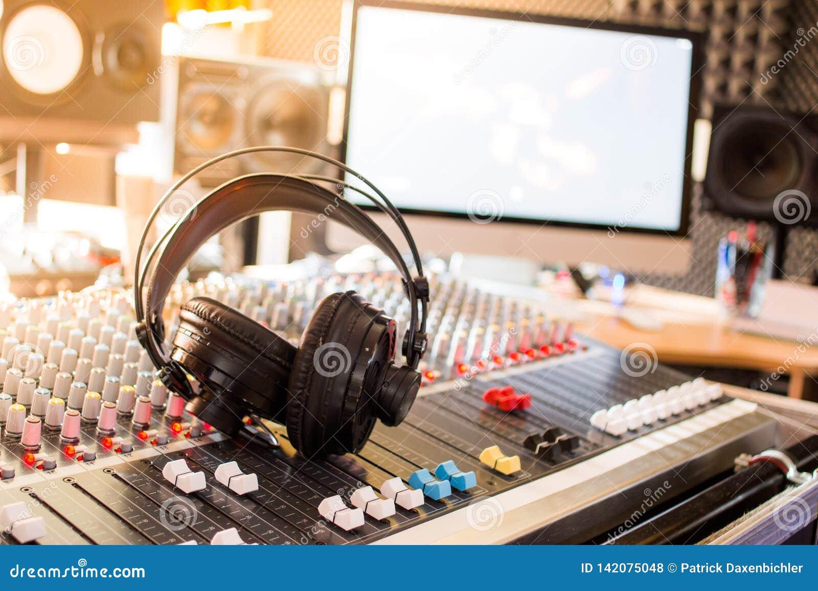 Estação de rádio: Fones de ouvido em uma mesa do misturador em um estúdio de gravação sonora profissional
