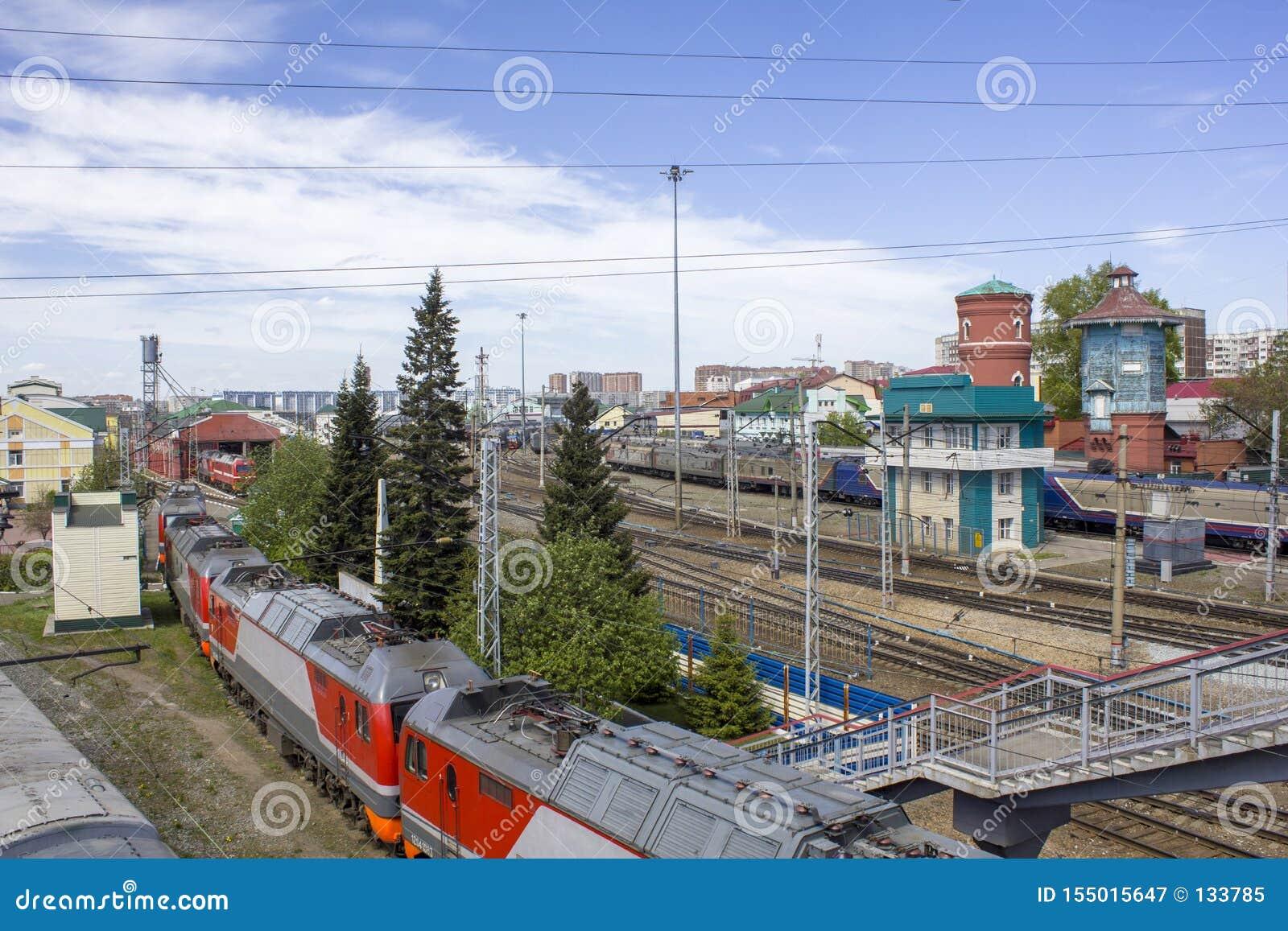 Estação de trem com muitos caminhos de ferro e a composição do trem com os carros no fundo da cidade moderna, aéreo